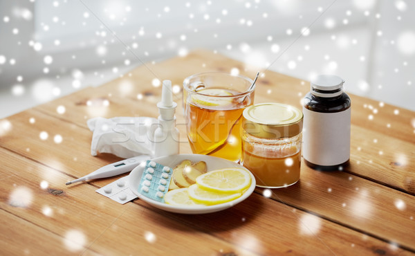 drugs, thermometer, honey and cup of tea on wood Stock photo © dolgachov