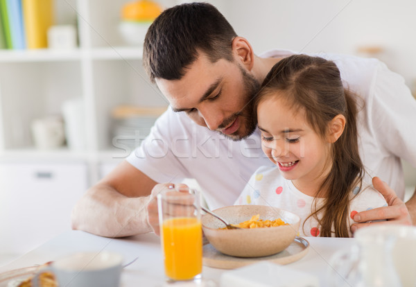 happy family eating flakes for breakfast at home Stock photo © dolgachov