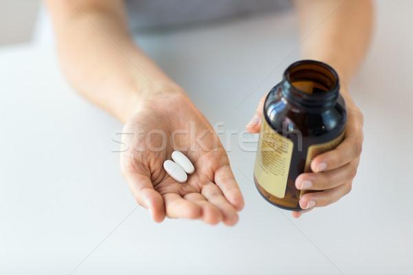 close up of hands holding medicine pills and jar Stock photo © dolgachov