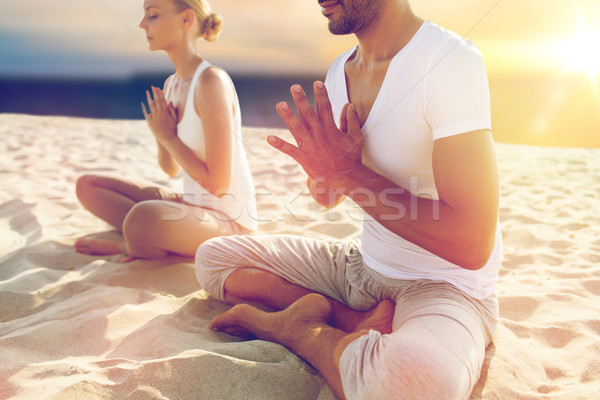 close up of couple meditating on beach Stock photo © dolgachov