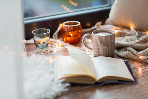 book and coffee or hot cchocolate on window sill Stock photo © dolgachov