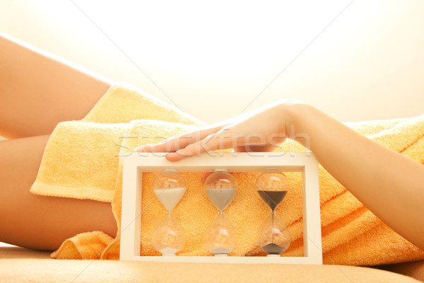 female hands and legs in spa salon with a sandglass Stock photo © dolgachov