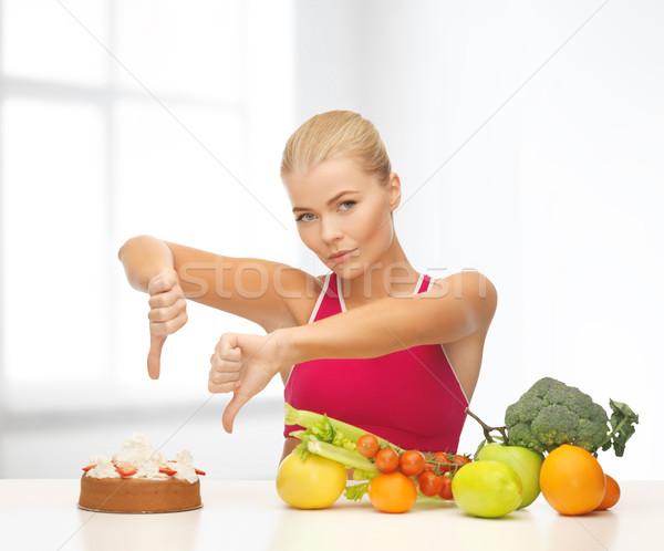 woman with fruits showing thumbs down to cake Stock photo © dolgachov