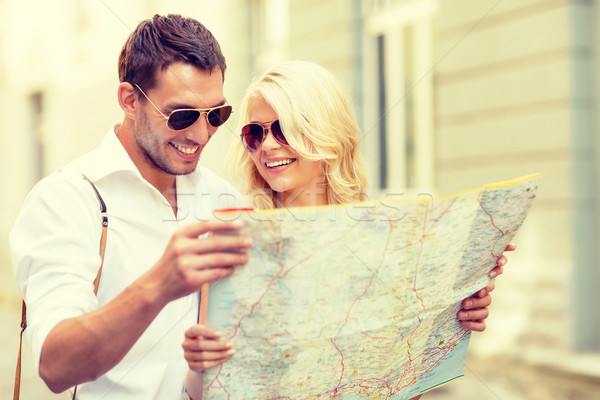 Stock photo: smiling couple in sunglasses with map in the city