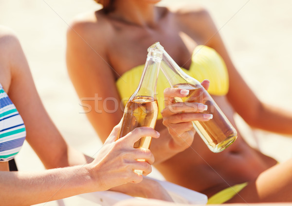 girls in bikinis with drinks on the beach chairs Stock photo © dolgachov