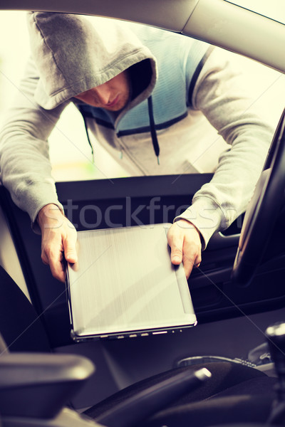 thief stealing laptop from the car Stock photo © dolgachov