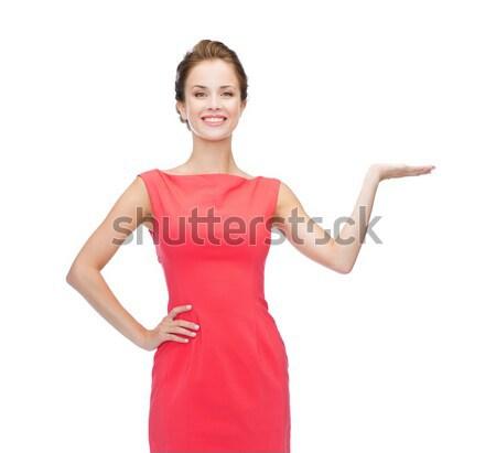 Mosolygó nő tart valami képzeletbeli pálmafák hirdetés Stock fotó © dolgachov