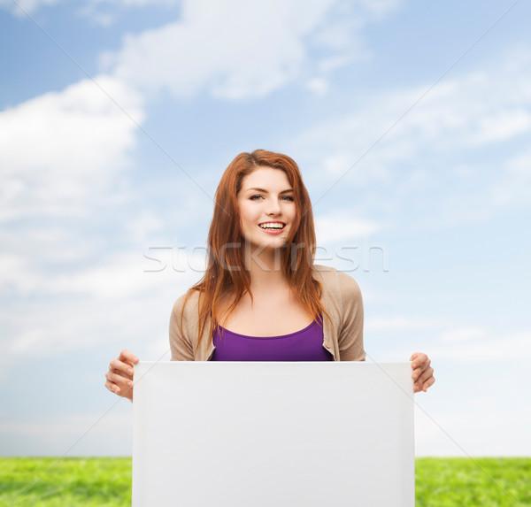 smiling teenage with white board Stock photo © dolgachov