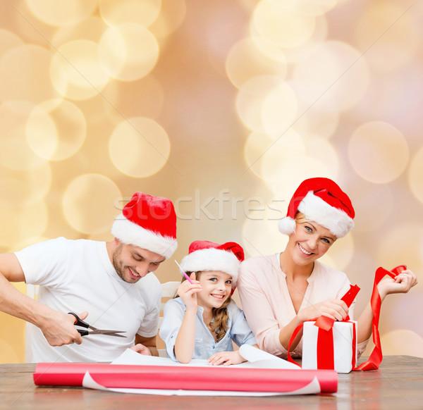 Boldog család mikulás segítő sapkák csomagol ajándék Stock fotó © dolgachov