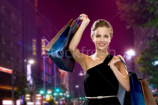 Mosolygó nő estélyi ruha bevásárlótáskák vásárlás vásár ajándékok Stock fotó © dolgachov
