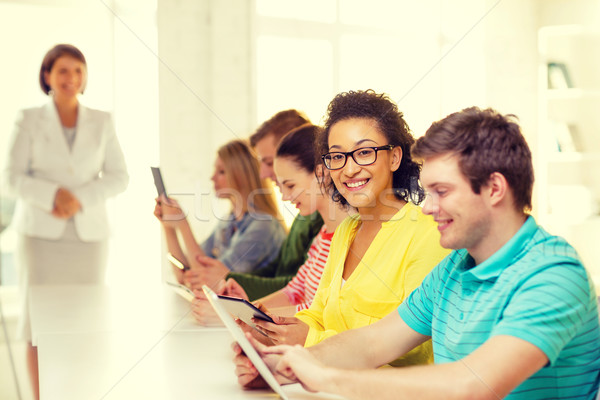 smiling female students with tablet pc at school Stock photo © dolgachov
