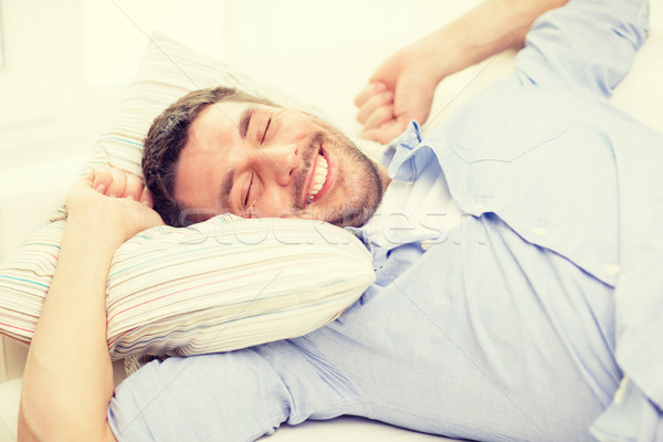 Stock photo: smiling young man lying on sofa at home