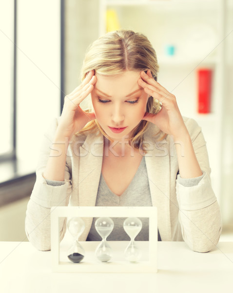 tired woman behind the table with hourgalss Stock photo © dolgachov