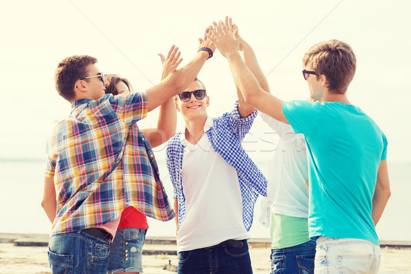 group of smiling friends making high five outdoors Stock photo © dolgachov