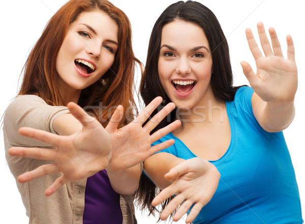 two smiling girls showing their palms Stock photo © dolgachov