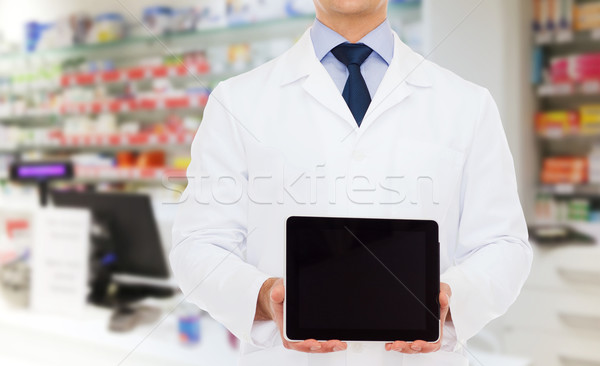 male doctor with tablet pc at drugstore Stock photo © dolgachov