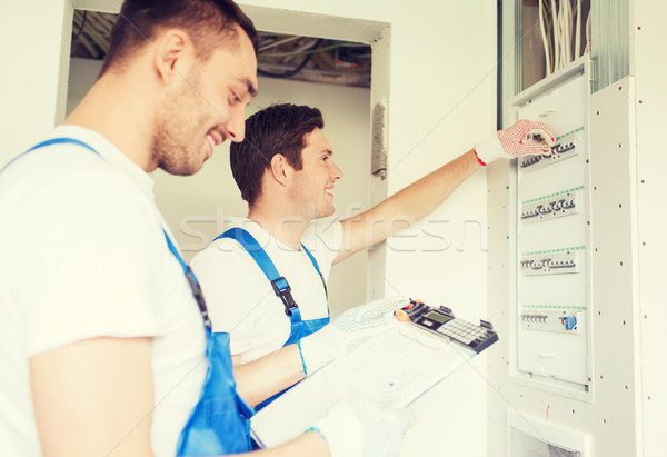 builders with clipboard and electrical panel Stock photo © dolgachov