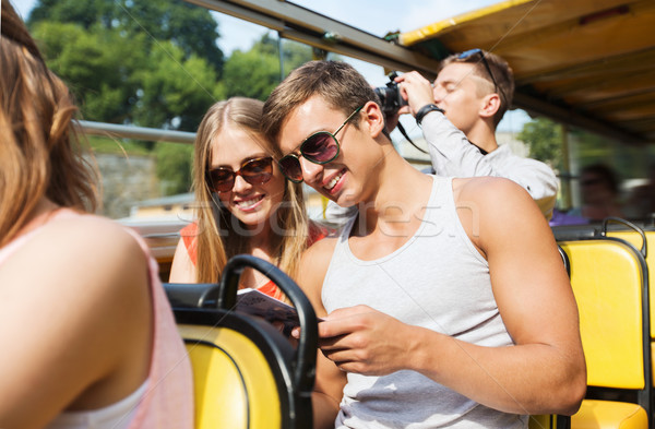 happy couple with guidebook traveling by tour bus Stock photo © dolgachov