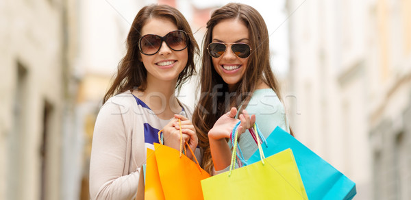 smiling girls in sunglasses with shopping bags Stock photo © dolgachov