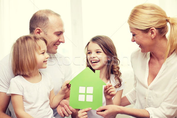 smiling parents and two little girls at new home Stock photo © dolgachov