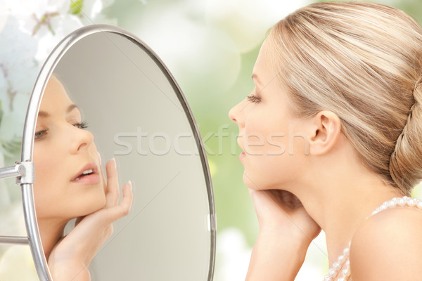 beautiful woman with pearl necklace and mirror Stock photo © dolgachov