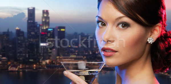 woman holding cocktail over singapore night city Stock photo © dolgachov