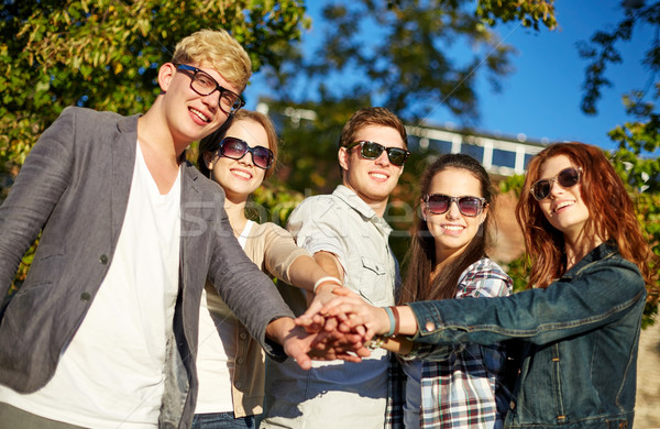 group of students or teenagers with hands on top Stock photo © dolgachov