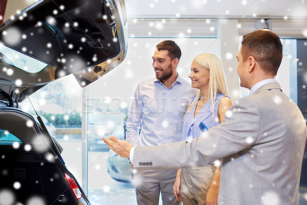 Stock photo: happy couple with car dealer in auto show or salon