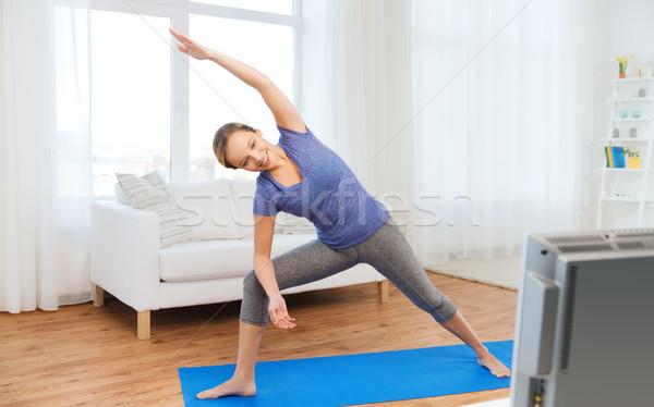 woman making yoga bikram triangle pose on mat Stock photo © dolgachov
