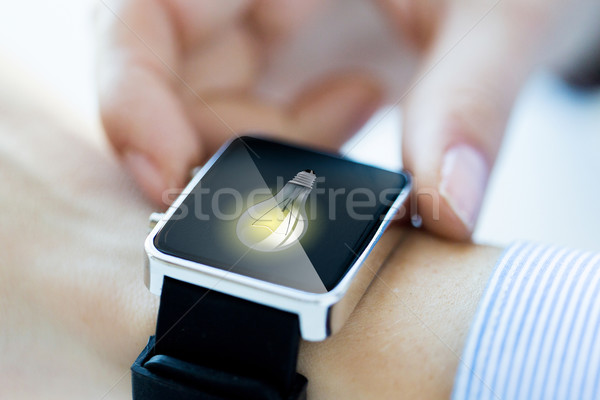 close up of hands with lightbulb on smartwatch Stock photo © dolgachov