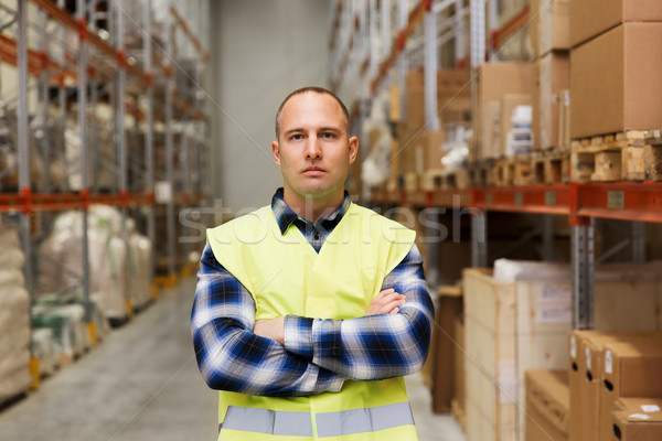 man in reflective safety vest at warehouse Stock photo © dolgachov