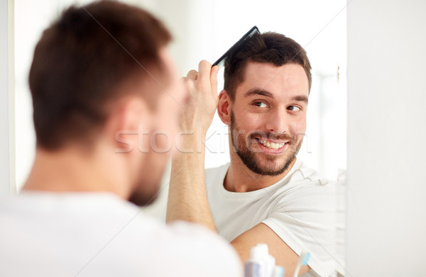 happy man brushing hair  with comb at bathroom Stock photo © dolgachov