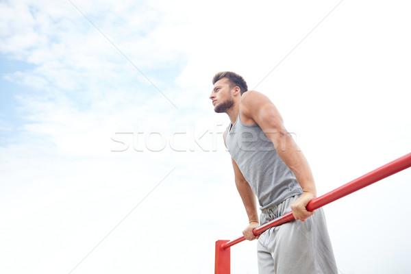 young man exercising on horizontal bar outdoors Stock photo © dolgachov