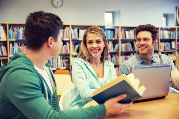 happy students with laptop and book at library Stock photo © dolgachov