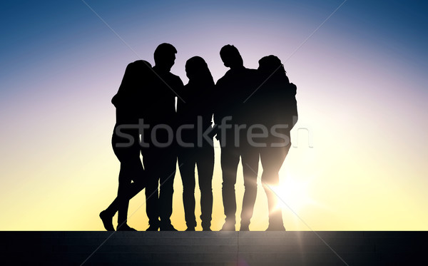 silhouettes of friends sitting on stairs over sun Stock photo © dolgachov