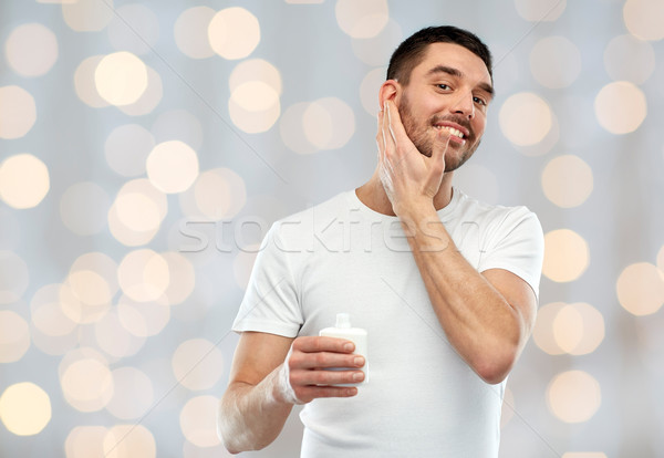 Feliz moço creme loção cara Foto stock © dolgachov