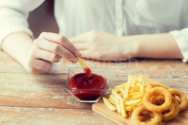 close up of hand dipping french fries into ketchup Stock photo © dolgachov