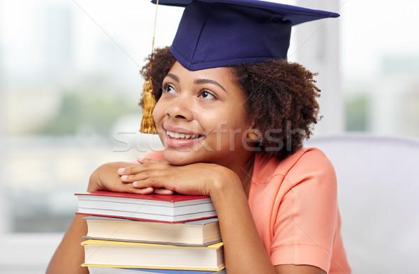 Gelukkig afrikaanse vrijgezel meisje boeken home Stockfoto © dolgachov