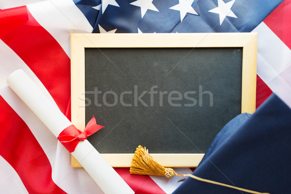 board, bachelor hat and diploma on american flag Stock photo © dolgachov