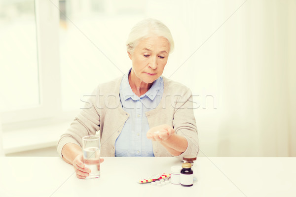 senior woman with water and medicine at home Stock photo © dolgachov