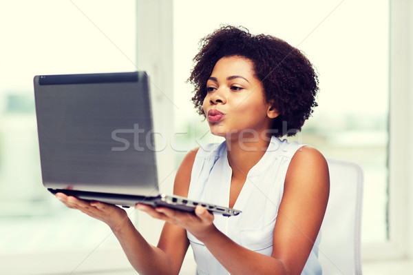 african woman sending kiss to laptop computer Stock photo © dolgachov