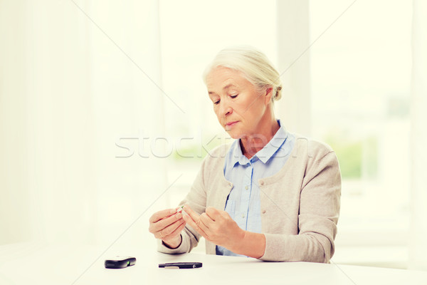 senior woman with glucometer checking blood sugar Stock photo © dolgachov