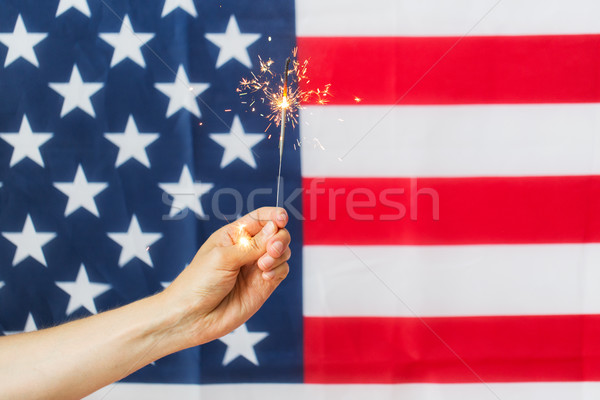 close up of hand with sparkler over american flag Stock photo © dolgachov