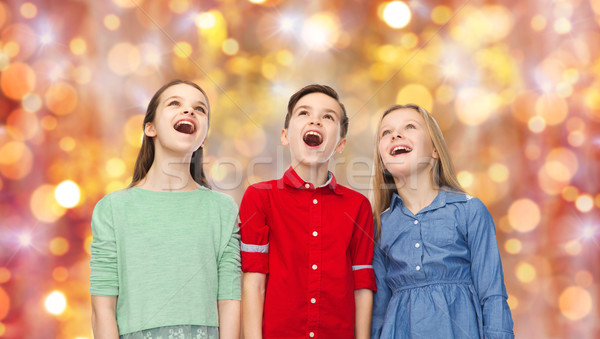 amazed children looking up over holidays lights Stock photo © dolgachov