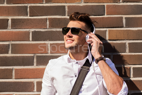 young man in headphones over brickwall Stock photo © dolgachov