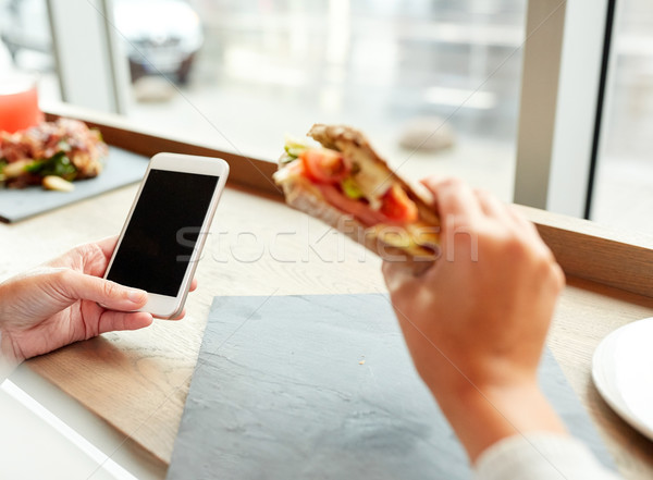 woman with smartphone and sandwich at restaurant Stock photo © dolgachov