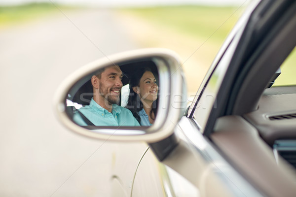 side mirror reflection of happy couple driving car Stock photo © dolgachov