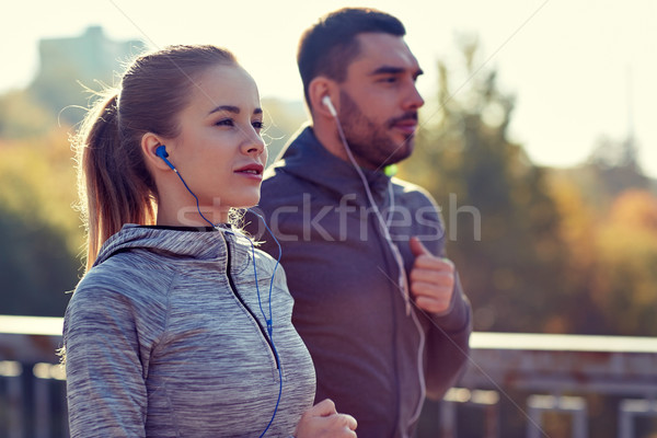 happy couple with earphones running in city Stock photo © dolgachov