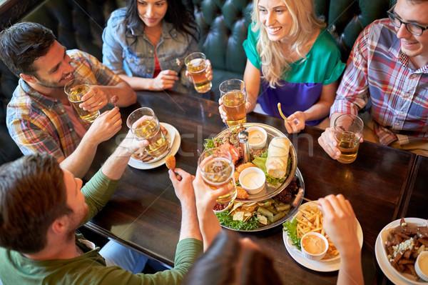 Gelukkig vrienden eten drinken bar pub Stockfoto © dolgachov