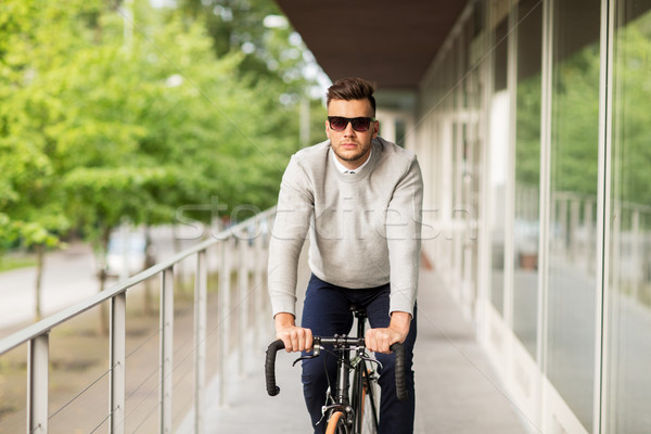 young man in shades riding bicycle on city street Stock photo © dolgachov